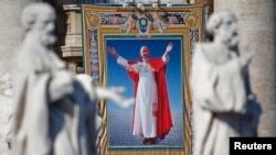 FILE - The tapestry with the image of Pope Paul VI is unveiled as Pope Francis celebrates the mass for his beatification in St. Peter's square at the Vatican, Oct. 19, 2014.