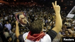 A protester holds up a poster with an image of former Egypt president Gamal Abdel Nasser during the anniversary of the 1952 Egyptian revolution at Tahrir Square in Cairo, July 23, 2012.