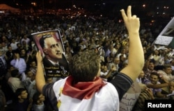 FILE - A protester holds up a poster with an image of former Egypt president Gamal Abdel Nasser during the anniversary of the 1952 Egyptian revolution at Tahrir Square in Cairo, July 23, 2012.