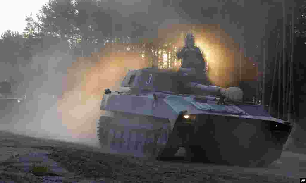 A soldier surrounded by smoke and dust sits on top of a Belarus army self-propelled artillery tank headed to rehearse for the Independence Day military parade on the outskirts of Minsk.