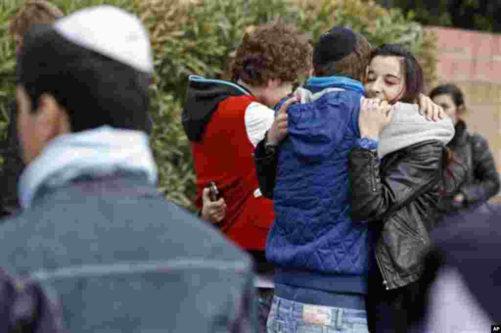 Students comfort each other at the Ozar Hatorah Jewish school where a gunman opened fire killing four people in Toulouse, southwestern France, Monday, March 19, 2012. A father and his two sons were among four people who died Monday when a gunman opened fi
