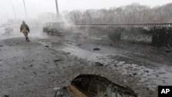 A Pro-Russian rebel walks past a car destroyed by a rocket during recent shelling in Donetsk, Ukraine, Monday, Feb. 9, 2015.