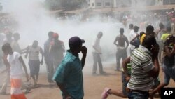 Opposition protesters disperse after tear gas is fired in their midst, in Conakry, Guinea, February 27, 2013.