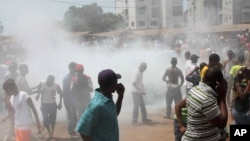 Opposition protesters disperse after tear gas is fired in their midst, in Conakry, Guinea, February 27, 2013 file photo.