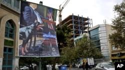 Tấm áp phích vẽ hình một nhà thương thuyết Mỹ mặc áo vest ngồi ở bàn đàm phán với một chú chó bên cạnh, được treo tại quảng trường Palestine, trong thủ đô Tehran, Iran, 27/10/13