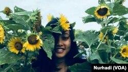 Lisa Anggraini, salah seorang pengunjung berselfie di antara bunga matahari di kawasan Samas, Yogyakarta. (Foto: VOA/Nurhadi)