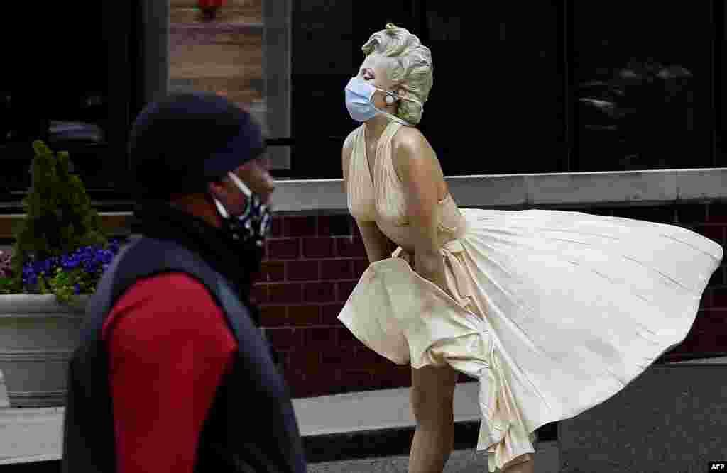 Човек со маска покрај скулптура на Мерилин Монро која исто така има маска во Мериленд. (Olivier DOULIERY / AFP)