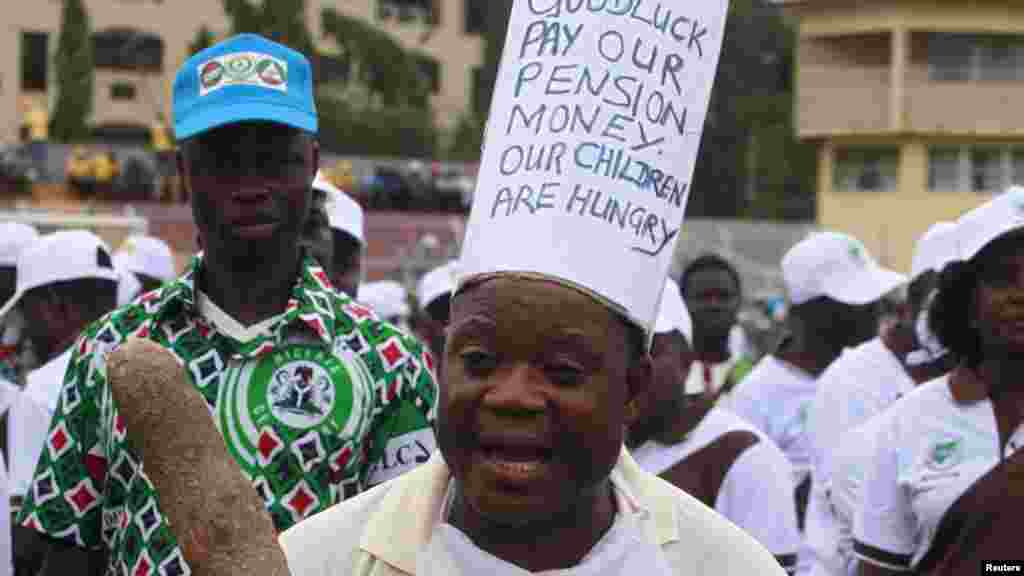 A worker holding a yam tuber with slogans on his clothes, protests during a parade marking Workers' Day in Nigeria, May 1, 2013.