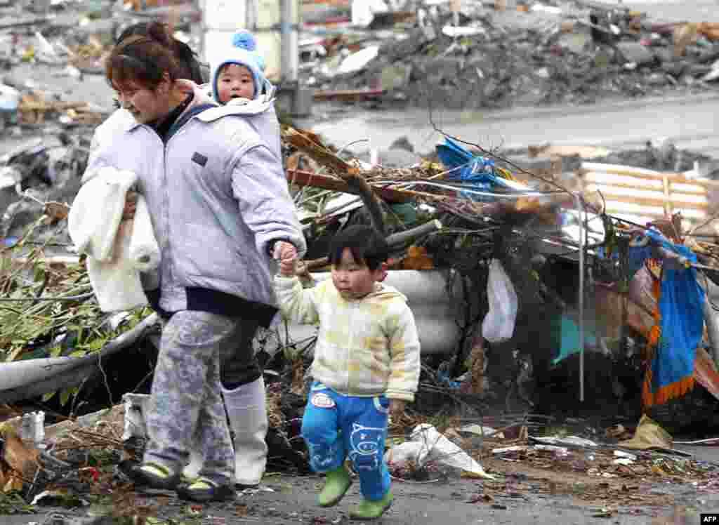 Семья проходит мимо развалин после землетрясения и цунами в городе Минамисанрику, Япония, 16 марта 2011г.