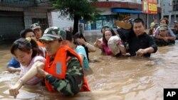 Des policiers évacuent les habitants d'une zone frappée par des inondations à Bijie, dans le soud-ouest de Guizhou, Chine, 30 juin 2006.