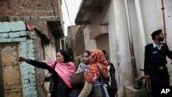 1월 30일 촬영된 사진에서 파키스탄 경찰이 소아마비 예방주사를 놓는 보건 요원들을 보호하고 있다.