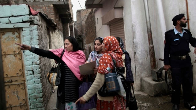 In this Jan. 30, 2013 photo, a Pakistani police officer, right, guards a group of health workers going from house to house to give polio vaccines to children in Islamabad, Pakistan.