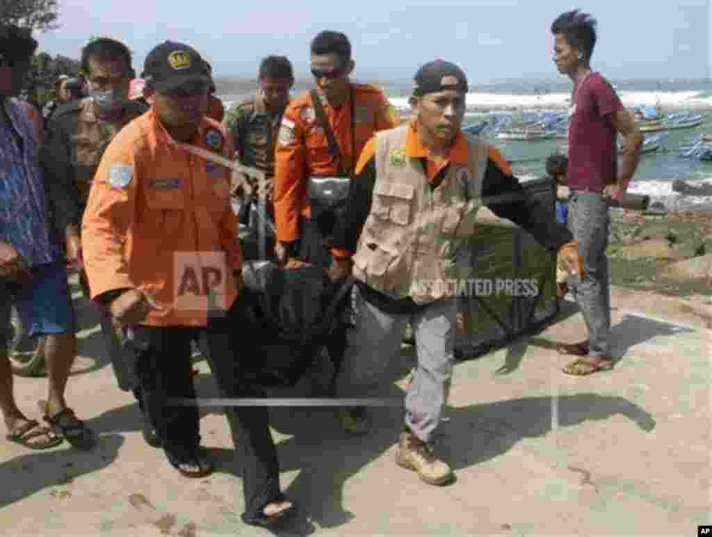 Rescuers carry the body of a victim killed after a boat carrying asylum seekers sank off West Java, Indonesia, July 24, 2013.