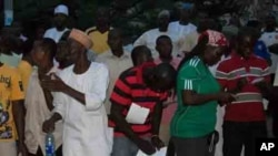 Voters and party agents recording election results at a polling station in Abuja, Nigeria's capital