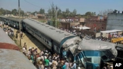 Tim SAR India berupaya menolong korban kecelakaan kereta api di dekat desa Bachhrawan, Uttar Pradesh, India (20/3). (AP Photo/Press Trust of India)