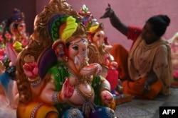 Seorang pengrajin mendekorasi patung dewa Hindu berkepala gajah Lord Ganesha menjelang festival Ganesh Chaturthi di New Delhi, 14 Agustus 2021. (Foto: Sajjad HUSSAIN / AFP)