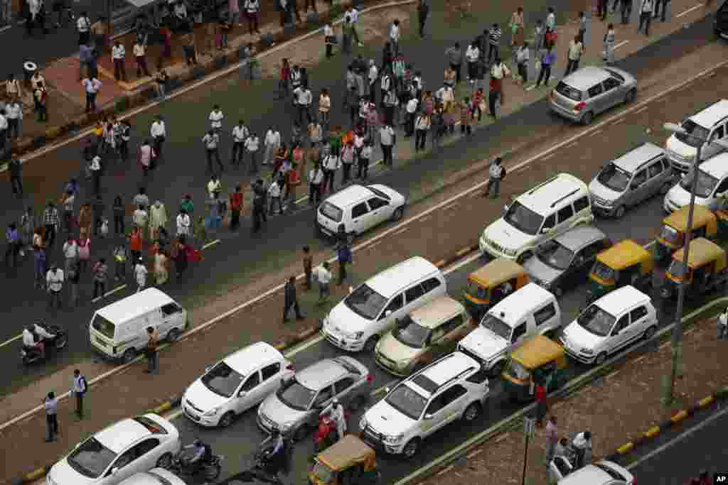 Commuters stand on a busy road outside a Metro station after Delhi Metro rail services were disrupted following power outage in New Delhi, India, July 31, 2012