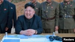 Le leader nord-coréen Kim Jon-Un entouré d'officiers de son armée, rit, avec un plan et des jumelles sur sa table, en Corée du Nord, 12 mars 2017.