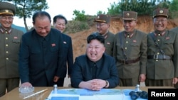 Le leader communiste nord-coréen Kim Jong-Un affiche un large sourire après un tir réussi d'un missile à longue portée, Corée du Nord, 12 mars 2017.