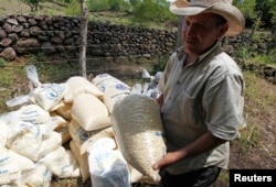 FILE - A farmer carries a bag of provision donated by the United Nations World Food Program (WFP) food reserves, during a distribution of food aid to families affected by the drought, in the village of Orocuina, Honduras, Aug. 28, 2014.