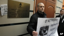 Russian opposition leader Sergei Udaltsov holds a placard during a rally outside the representative offices of the Astrakhan region during a rally in Moscow, April 9, 2012.