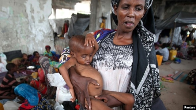 An internally displaced woman holds her malnourished son at a new settlement in Somalia's capital Mogadishu, July 19, 2011.