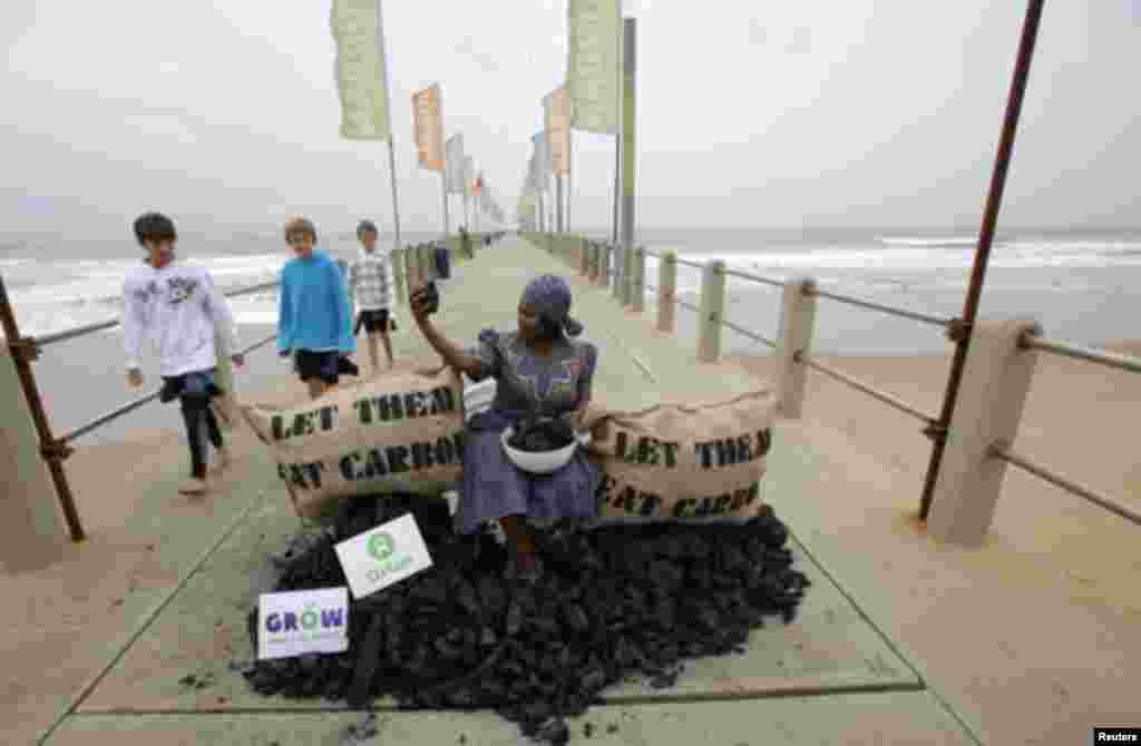 Busi Ndlovu, a member of the aid group Oxfam, stages a protest against the use of coal-based energy on Durban's beachfront, December 9, 2011. The city is hosting the United Nations Climate Change Conference (COP17) meeting. REUTERS/Mike Hutchings