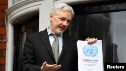 WikiLeaks founder Julian Assange holds a copy of a U.N. ruling as he makes a speech from the balcony of the Ecuadorian Embassy, in central London, Britain, Feb. 5, 2016.