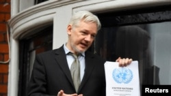 FILE - WikiLeaks founder Julian Assange holds a copy of a U.N. ruling as he makes a speech from the balcony of the Ecuadorian Embassy, in central London, Britain, Feb. 5, 2016.