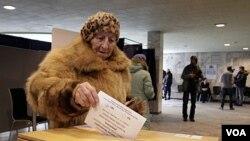 Seorang wanita Latvia memasukkan surat suaranya ke dalam kotak di sebuah TPS di Riga, Latvia (18/2).