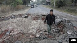 Dân làng Thái Lan đi qua một hố bom gần Sisaket ở Thái Lan, gần biên giới với Campuchia