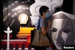香港支聯會營運的六四紀念館裡一名遊客在一塊刻有民主女神像的板子旁祈禱。