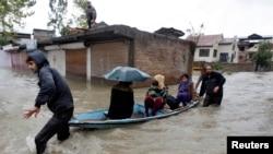 Trẻ em và phụ nữ được đưa qua một khu vực bị ngập lụt đến nơi an toàn hơn tại Srinagar, Ấn Độ, ngày 4/9/2014.