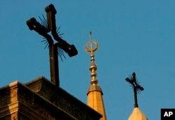 FILE - A minaret of the Mohammed al-Amin Mosque and two crosses on top of the Maronite St. George Cathedral are seen in downtown Beirut, Lebanon, Sept. 17, 2006.