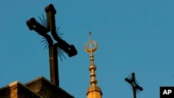 FILE - A minaret of the Mohammed al-Amin Mosque and two crosses on top of the Maronite St. George Cathedral are seen in downtown Beirut, Lebanon, Sept. 17, 2006. Muslims, by 2016, are expected to make up about 31 percent of world's population, trailing Christians by just one percent.