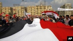 Egyptian anti-government demonstrators hold a huge national flag as they gather in Cairo's Tahrir square on February 9, 2011 on the 16th day of consecutive protests calling for the ouster of President Hosni Mubarak
