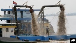 A Cambodian man controls pumps mounted on a ship to dredge sand in the middle of the Mekong River near Phnom Penh, Cambodia, Sunday, Oct. 9, 2011. (AP Photo/Heng Sinith)
