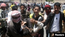 22일, 예멘 서남부 타이즈 시에서 시아파 후티 반군에 반대하는 시위자들이 반군과 충돌 과정에서 부상당한 한 남성을 옮기고 있다.