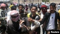 Taiz kentinde Huti milisleriyle çatışma sırasında yaralanan bir gösterici taşınırken