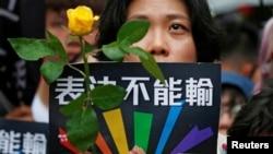 在台湾立法院就同性婚姻法案表决之际,同性婚姻支持者举着玫瑰花悼念那些因受歧视而自杀的人。(2019年5月17日)
