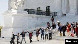 当美国最高法院审理奥巴马关于推迟遣返非法移民的政令是否违宪问题的时候,移民事务积极分子在法院外面手拉手(2016年4月18日)