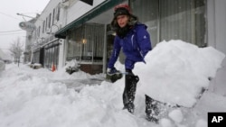 Alisa Riley, shovels snow from a sidewalk in front of a fitness center where she works in Scituate, Massachusetts, Jan. 22, 2014.