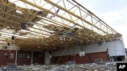Một lá cờ Mỹ bay trên nóc sân tập thể dục - đã bị hư hại sau trận lốc xoáy - của trường Trung học Henryville trong bang Indiana hôm 3/3/12