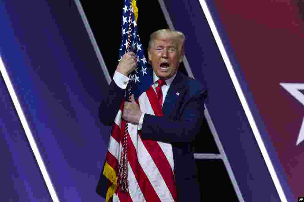 President Donald Trump hugs and kisses the American flag after speaking at Conservative Political Action Conference, CPAC 2020, at the National Harbor, in Oxon Hill, Maryland, Feb. 29, 2020.