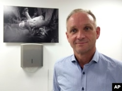 Mats Brannstrom poses besides a photo showing the birth of a baby of a mother with a womb transplant at Stockholm IVF fertility clinic in Stockholm, Sweden, Sept. 19, 2016.