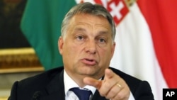Hungarian Prime Minister Viktor Orban addresses the media on the occasion of a meeting with Austrian Chancellor Werner Faymann and Vice Chancellor Reinhold Mitterlehner at the Hungarian Embassy in Vienna, Austria, Sept. 25, 2015.