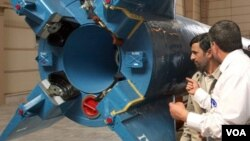 El mandatario Ahmadinejad observa uno de los cohetes que transportará el satélite hasta el espacio.