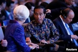Christine Lagarde, direktur pelaksana Dana Moneter Internasional (IMF), kiri, berbincang dengan Presiden Joko Widodo pada pembukaan pertemuan tahunan Dana Moneter Internasional – Bank Dunia 2018 di Nusa Dua, Bali, 12 Oktober 2018