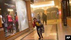 Una mujer que había permanecido escondida aprovecha para escapar durante los enfrentamientos en el centro comercial de Nairobi.