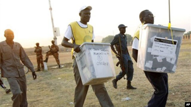 Election officials carry ballot boxes moments after polls closed in Juba, Southern Sudan, on January 15, 2011. South Sudan is due to hold a general election in July 2015.